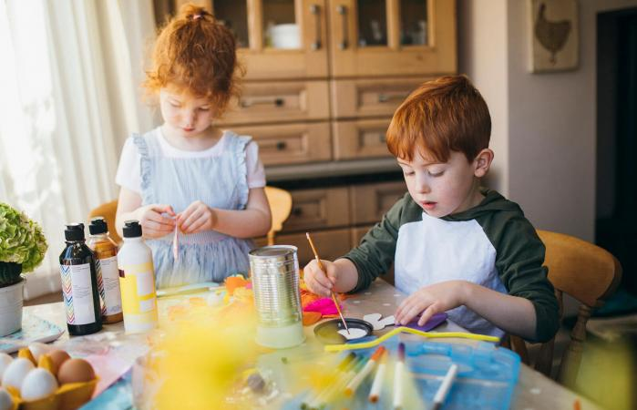 Two young children painting at home