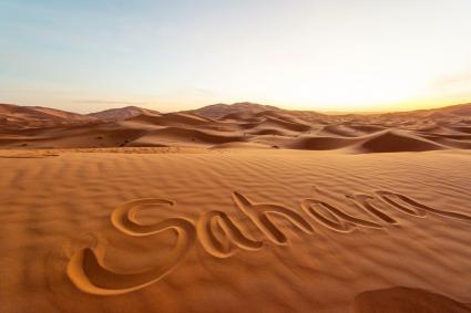 Sahara written on sand in desert, Morocco