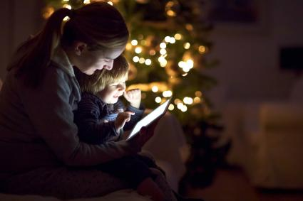 Mother with his son looking a digital tablet in the dark