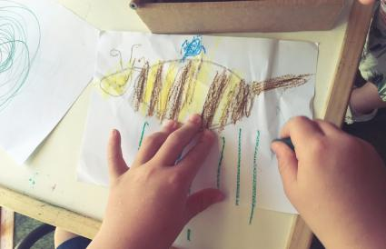 Child drawing a picture of a bee
