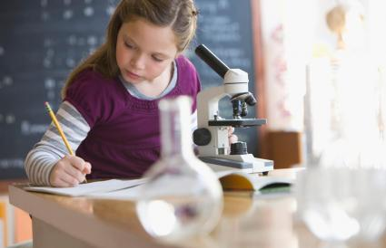 Caucasian girl looking into classroom microscope