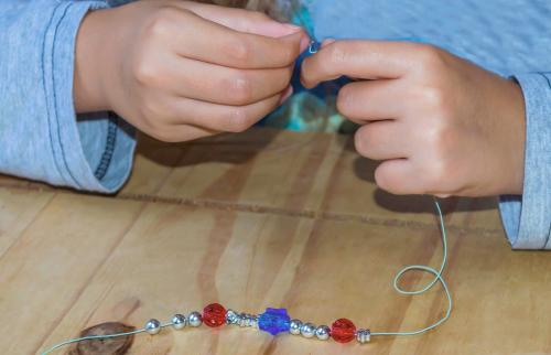 girl making a beaded bracelet