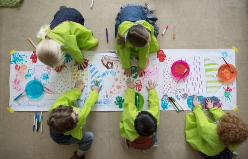 preschool students using finger paints on poster