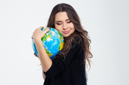 Happy cute woman hugging globe