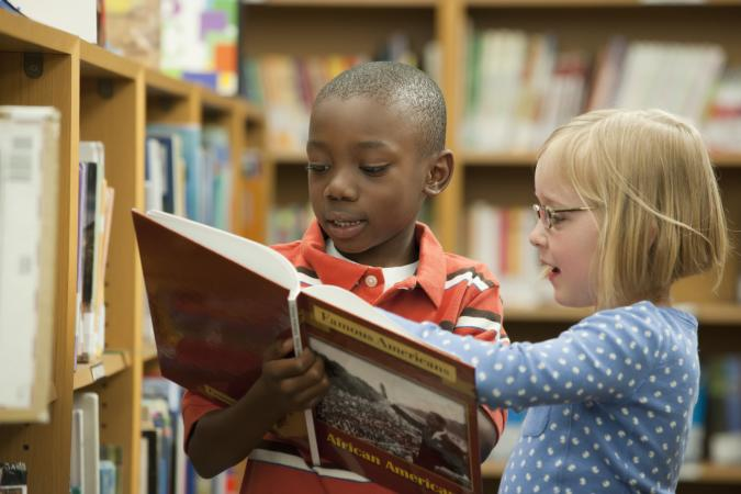 Boy and girl classmates sharing history book in library