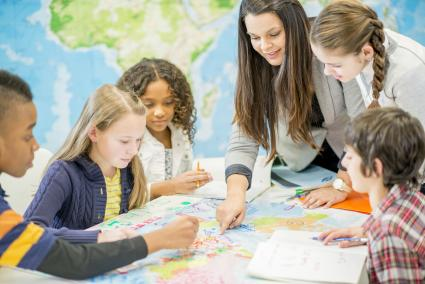 School children studying world map in geography class