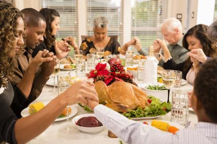 Family praying before eating Thanksgiving dinner