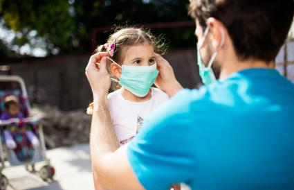 father applying mask to his daughter