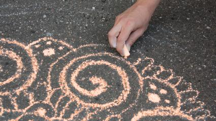 Drawing a Mandala design with sidewalk chalk.