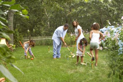 Couple playing croquet with their three daughters
