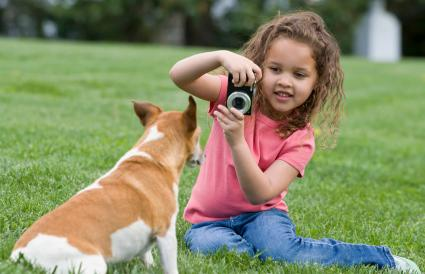 girl photographing dog