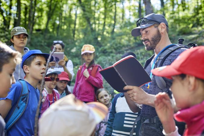 Man reading to kids on a field trip in forest