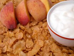 Healthy snack of peaches, yogurt, and corn flakes