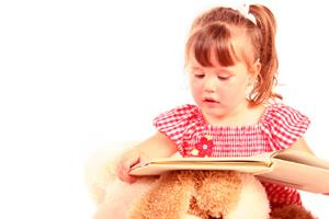 Image of a preschool girl trying to read a book