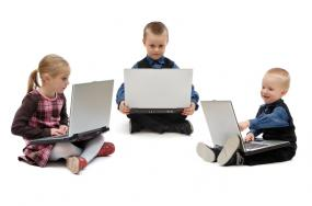 Iage of three young children using laptops