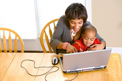Mom helping preschooler play an online game