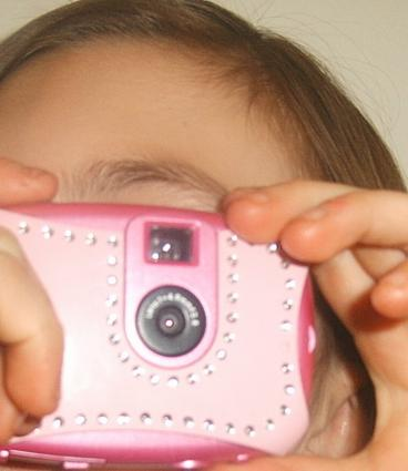 Little girl using a pink rhinestone kids' camera