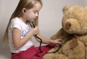 Girl examining a Teddy bear with a stethoscope