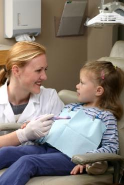 Image of a dentist examining a preschool girl's teeth