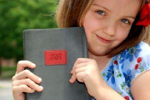 Happy preschool girl showing her Bible