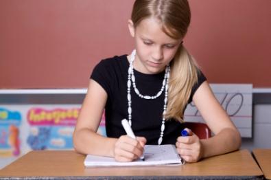 School girl writing in the classroom