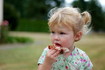 Toddler girl eating a sandwich at a picnic