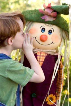 Little boy whispering in a scarecrow's ear