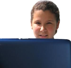 Young girl looking out from behind a laptop