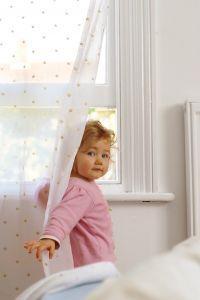 Toddler girl standing near her bedroom window