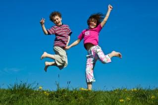 Kids jumping outside on a sunny day
