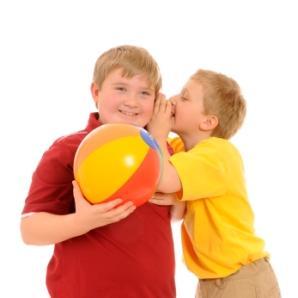 A boy whispering a joke in another boy's ear
