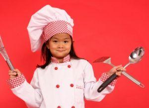 Image of a child chef holding cooking utensils