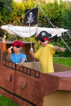 Boys playing pirates in a cardboard ship