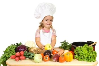 Toddler chef with a table of fresh vegetables