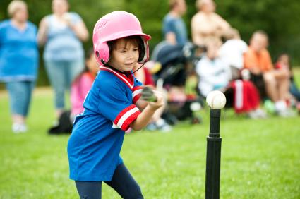 Little girl swinging at a softball