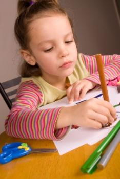 Little girl coloring a homemade birthday card