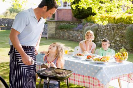 Parents and children at outdoor barbecue