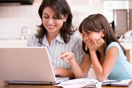 girl and mom looking at laptop