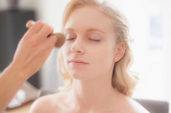 applying makeup on bride