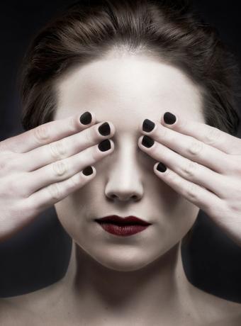 woman with short dark fingernail polish