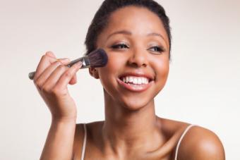 Lady applying blush on cheeks