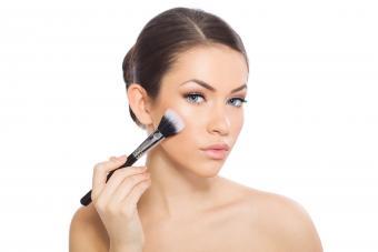 woman applying blush to cheeks