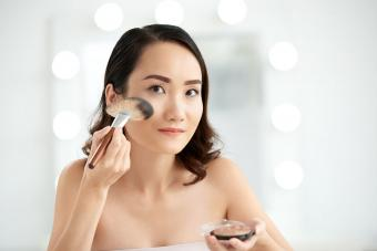 woman applying highlighter with makeup brush