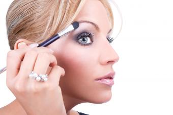 Woman applying highlighter to browbone