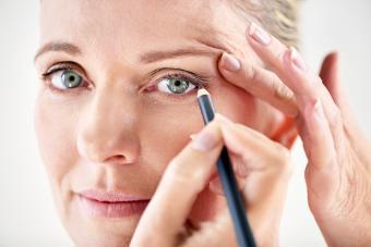 Mature woman applying eyeliner