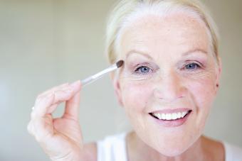 Senior woman applying eye make up