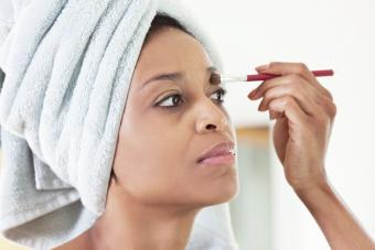 Woman wrapped in towel applying makeup