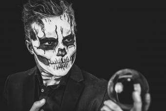 Young Man With Spooky Make-Up Holding Crystal Ball