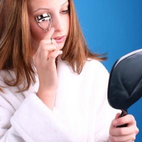 woman curling lashes in mirror