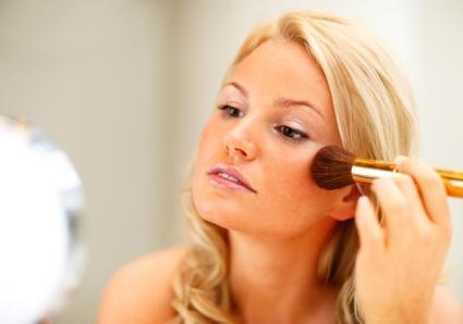 Applying blush to cheeks